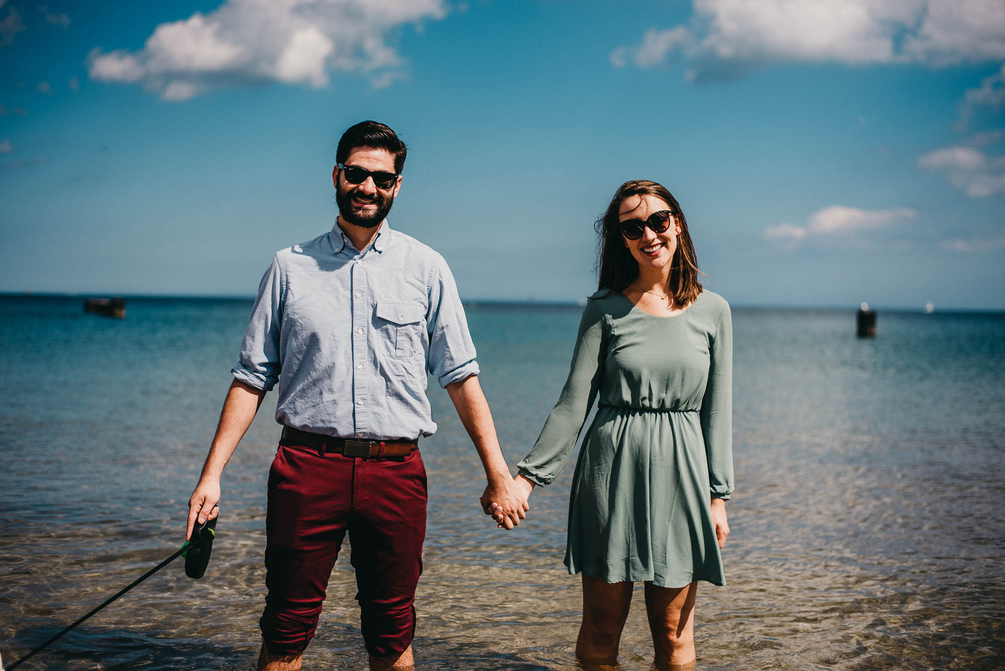 A man and woman holding hand while standing in Lake Michigan