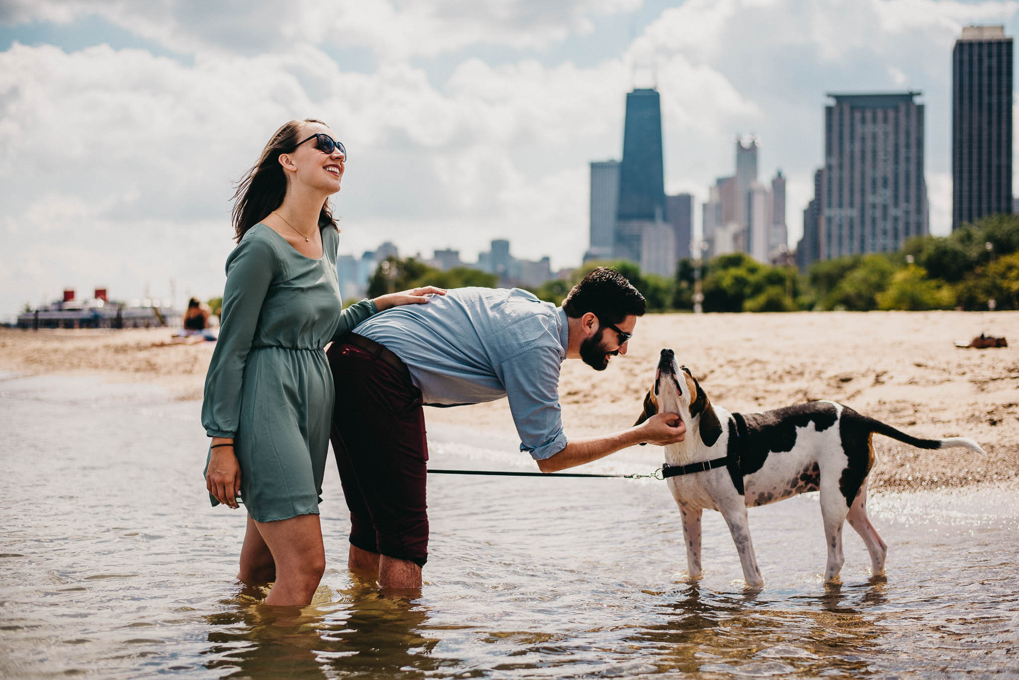Couple petting their dog on north Chicago beach