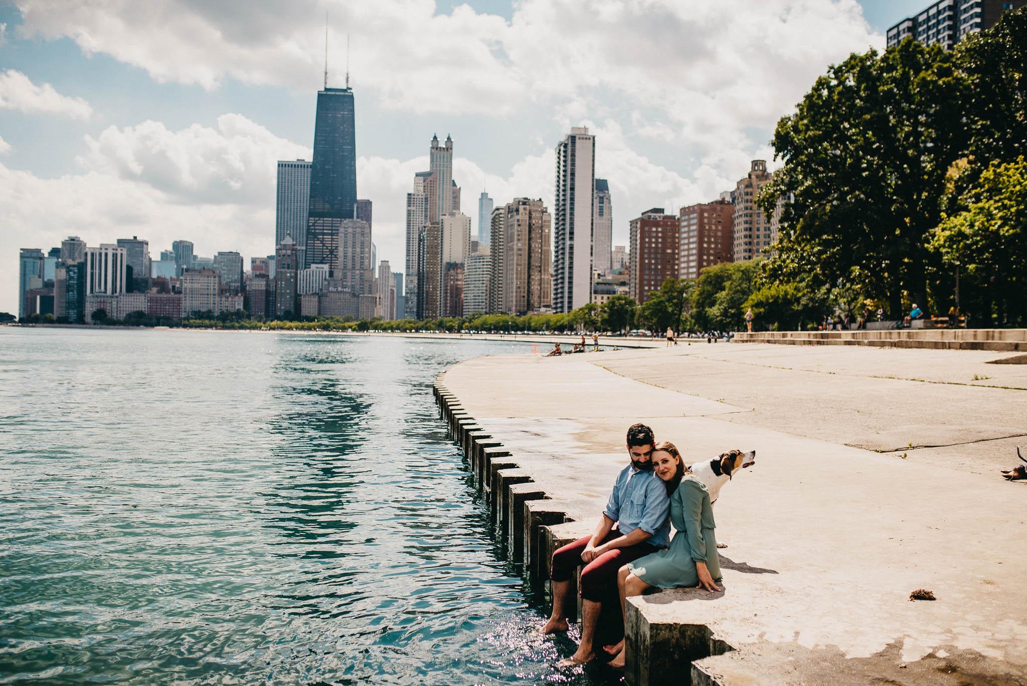 An engaged couple snuggling near lake Michigan