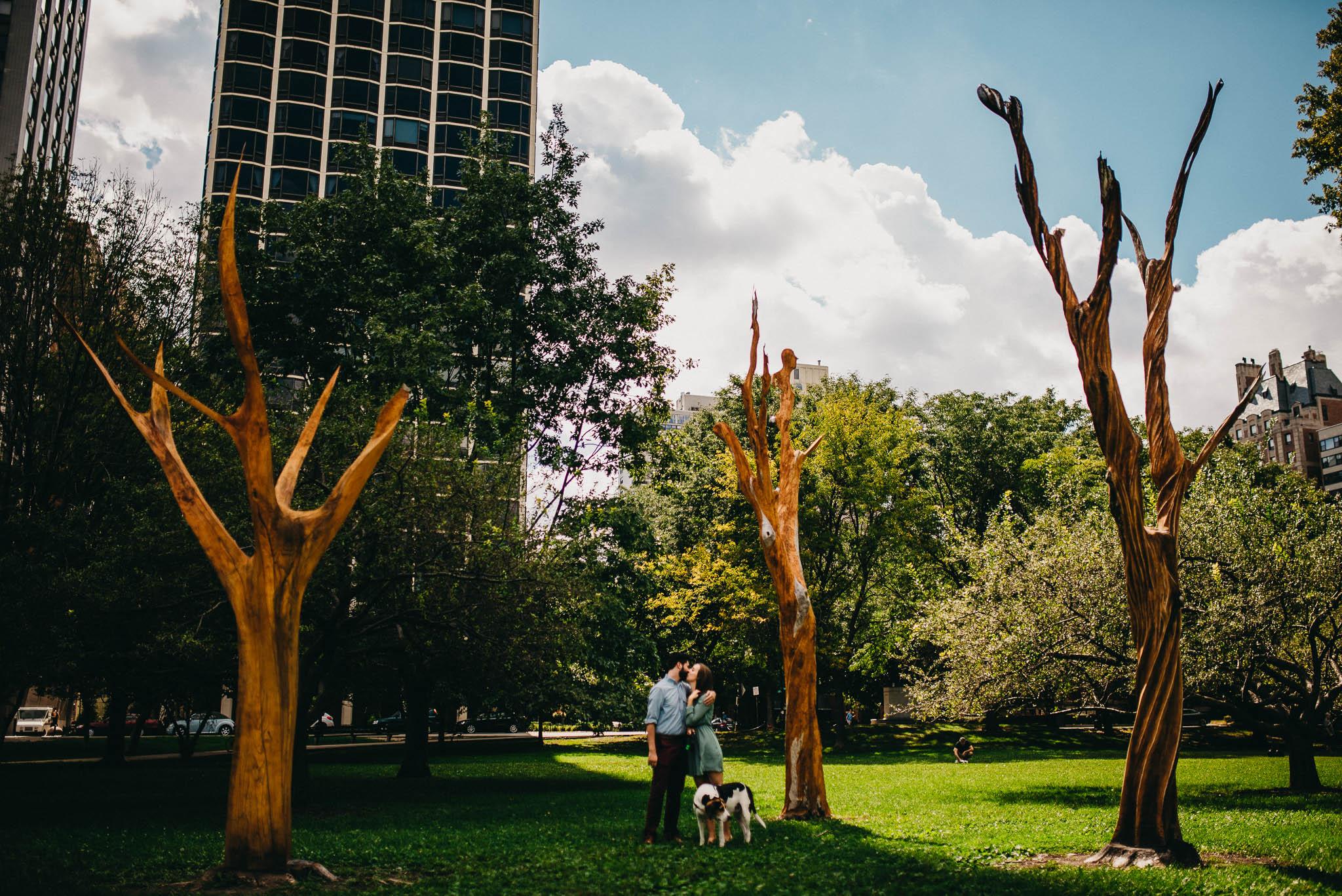 Engaged couple kissing near wood art installation