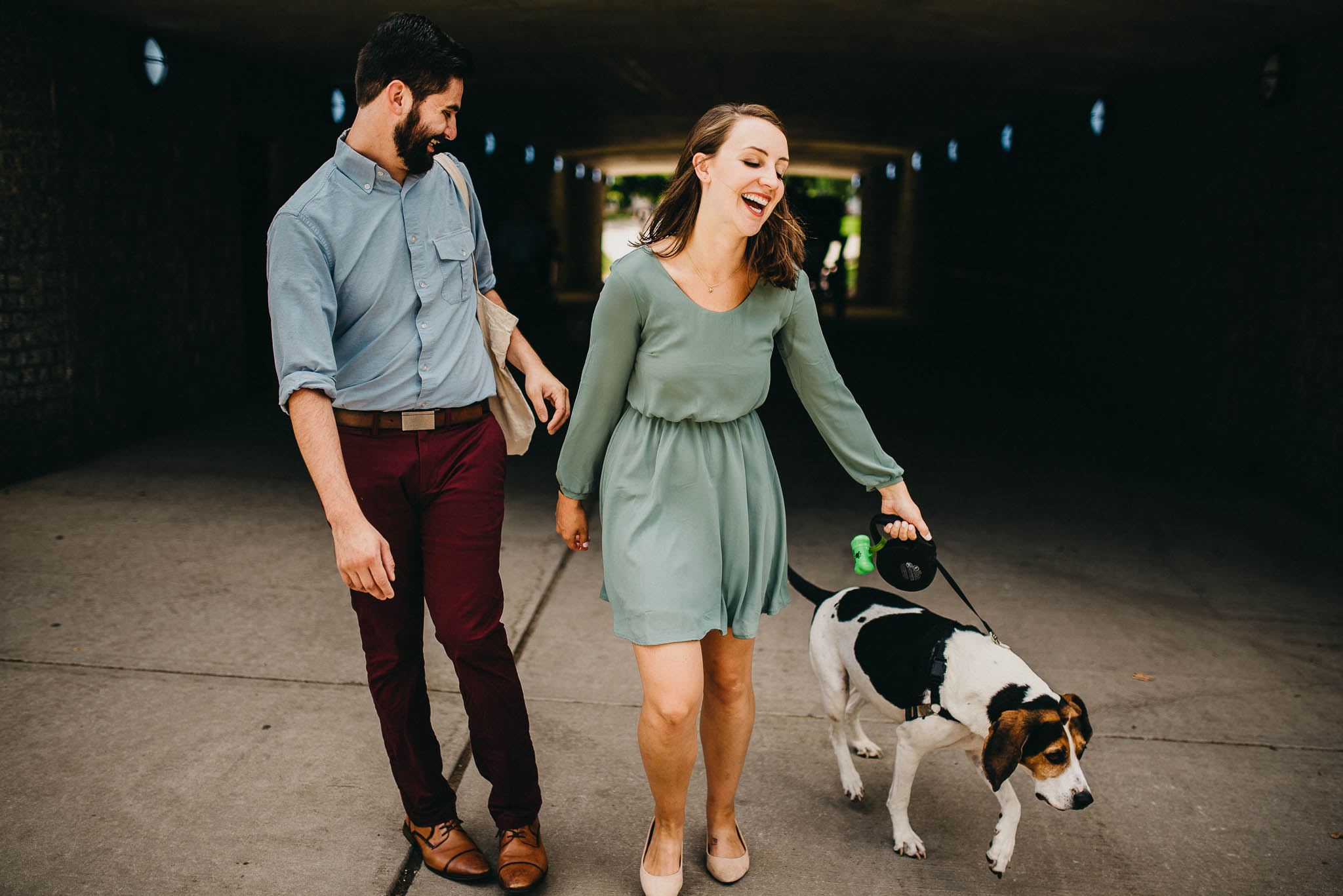 engaged couple laughing as dog barks at horses