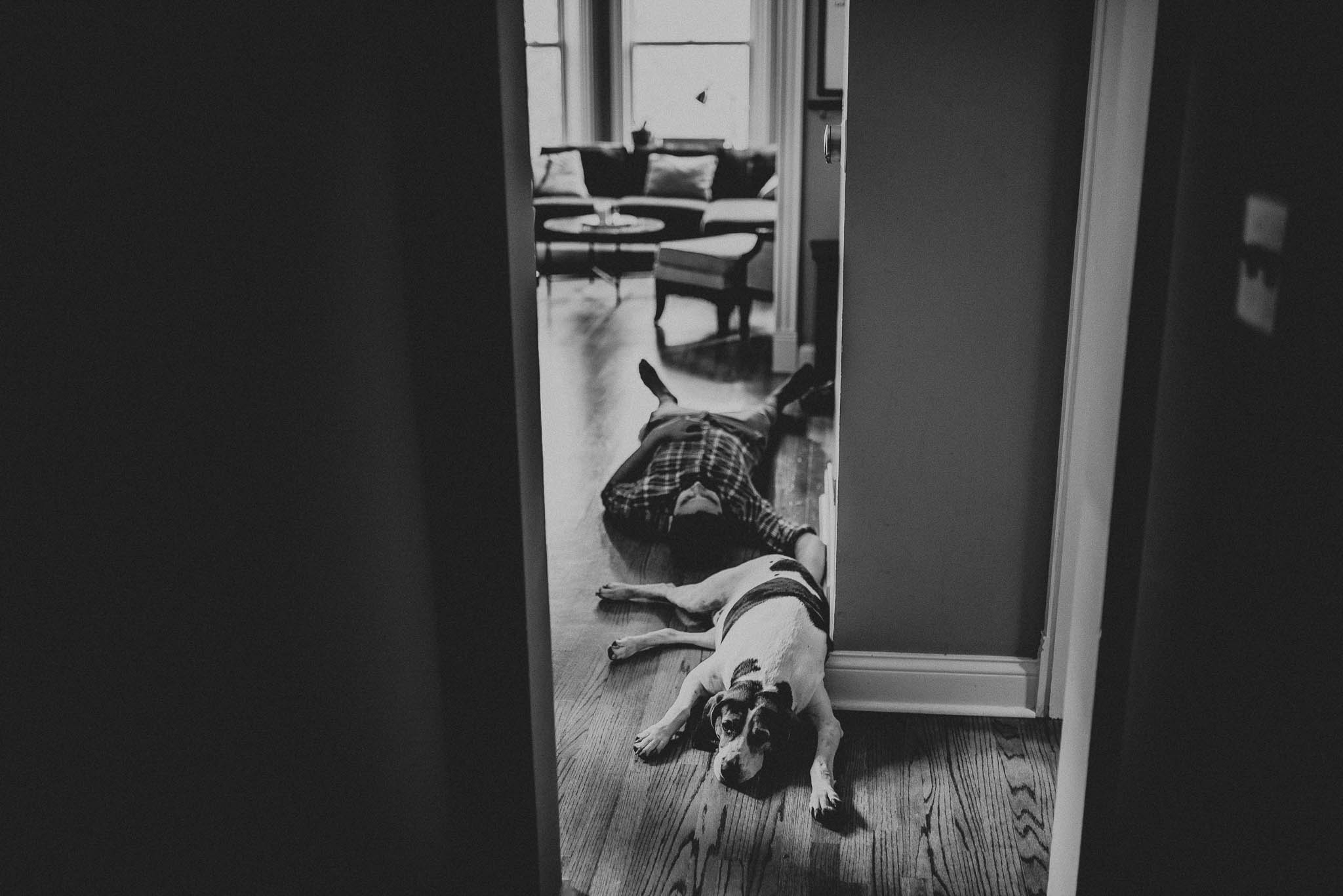 A dog and his owner laying in their hallway