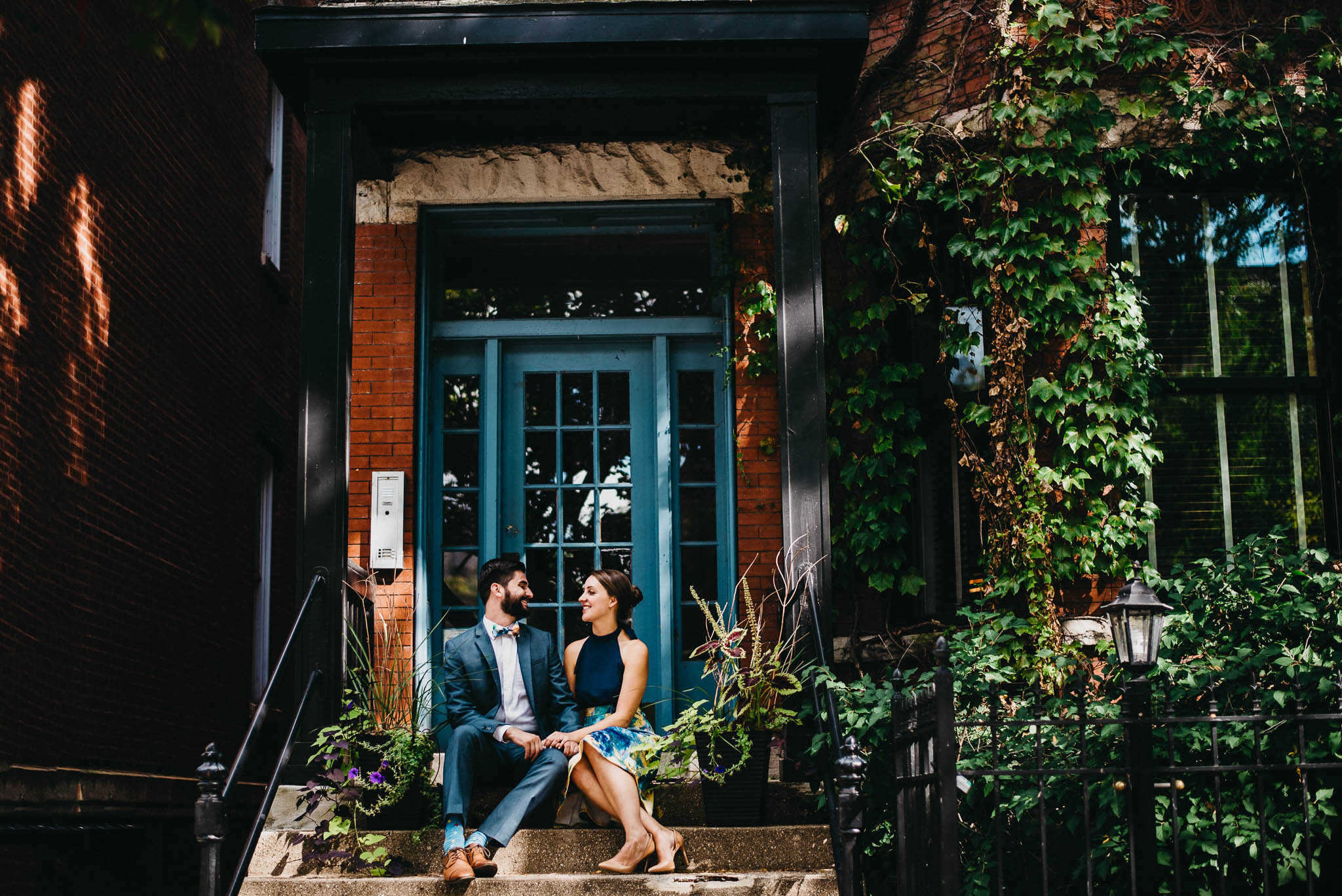 A couple dressed up for photos sitting on steps