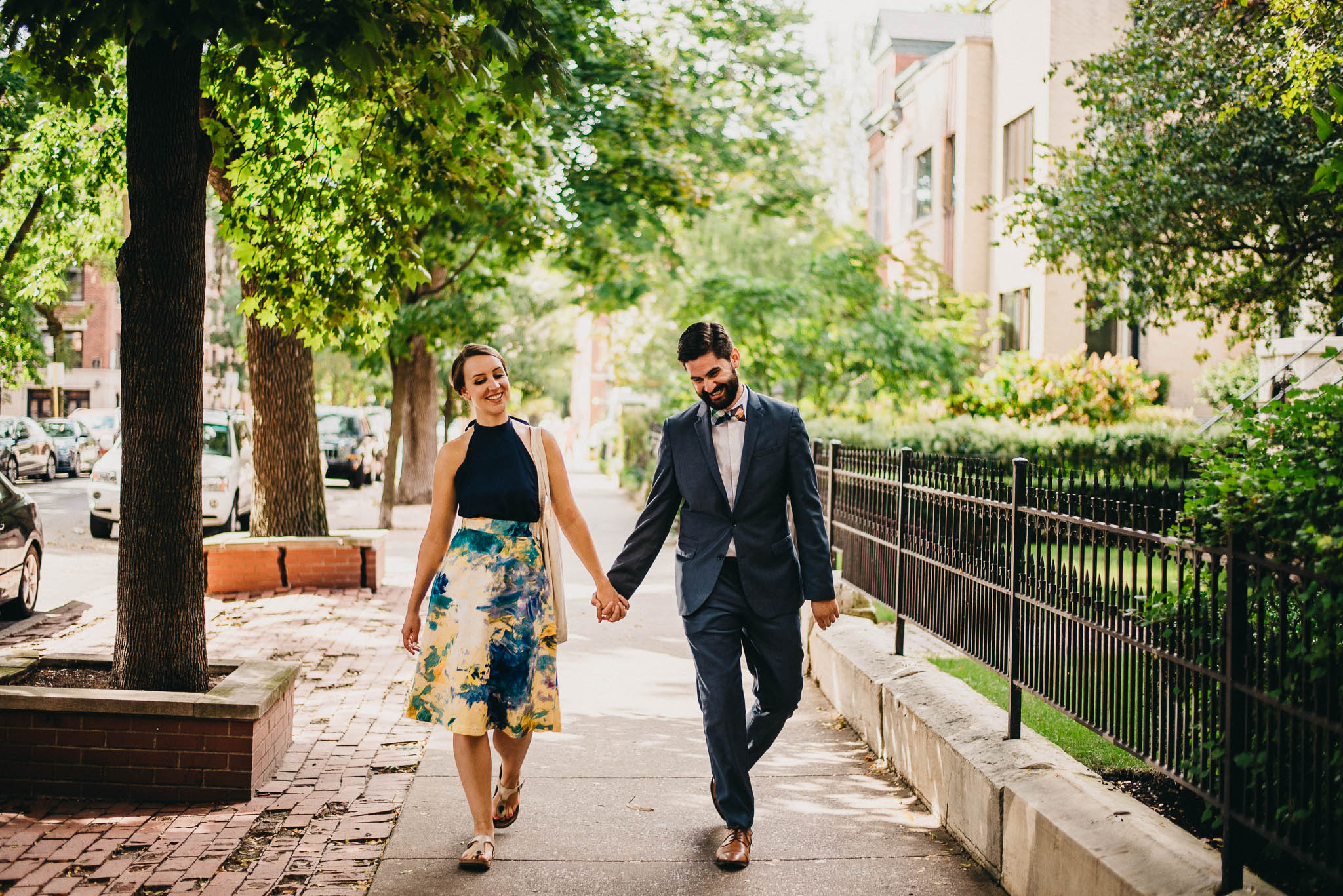 Engaged couple holding hand and walking down Chicago sidewalk
