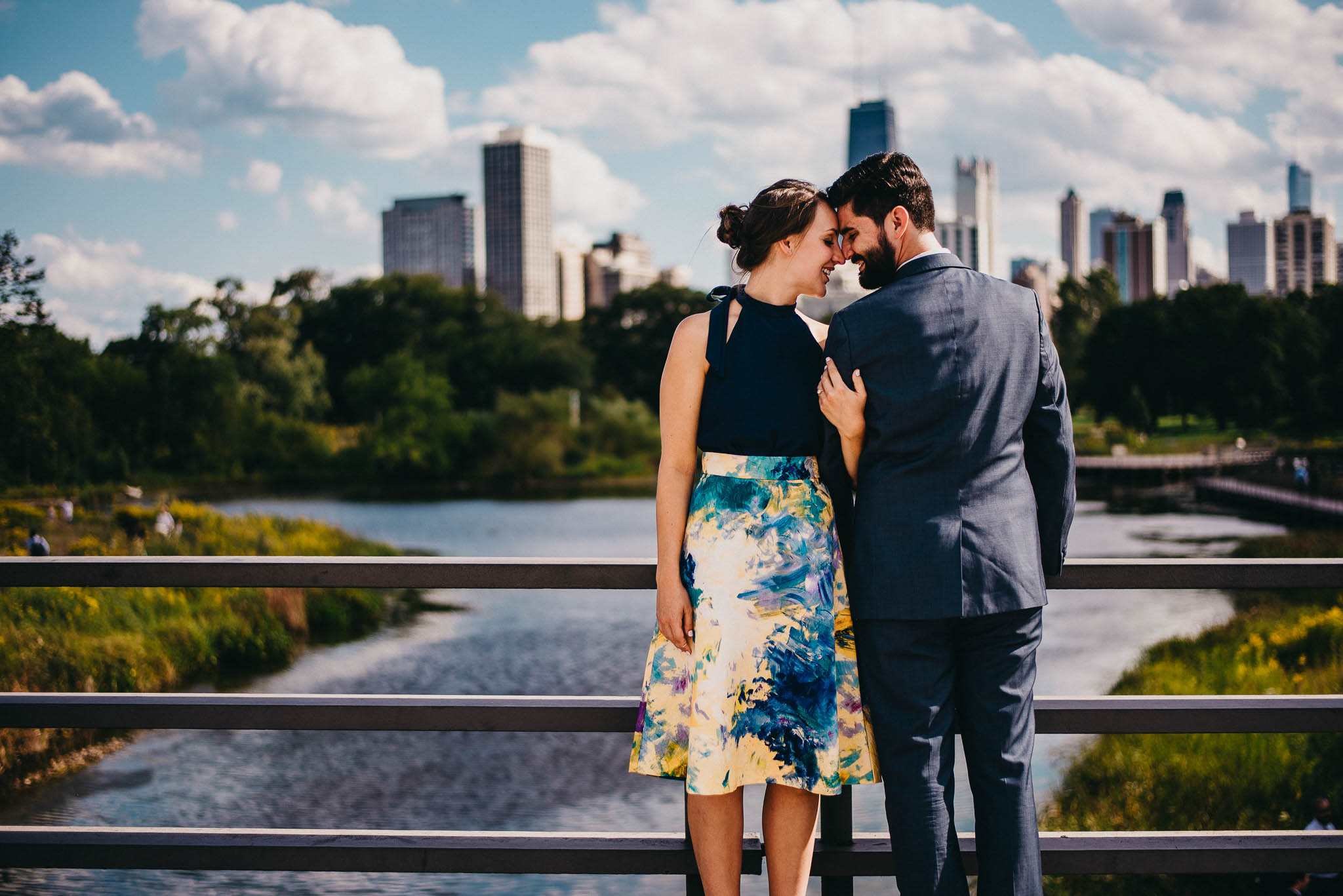 Engaged couple posing on foot bridge in Chicago park