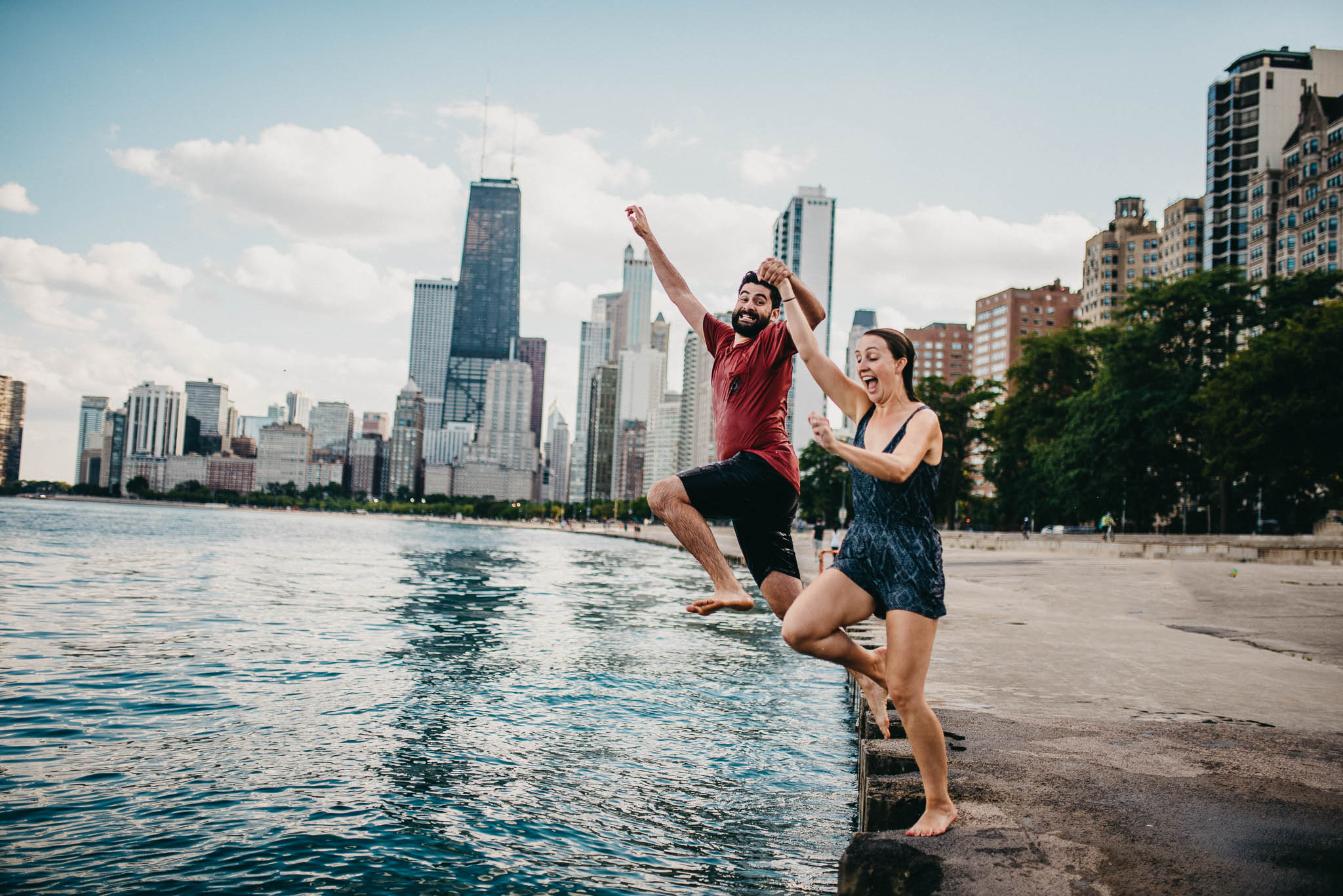 engagement photo of couple jumping into lake Michigan