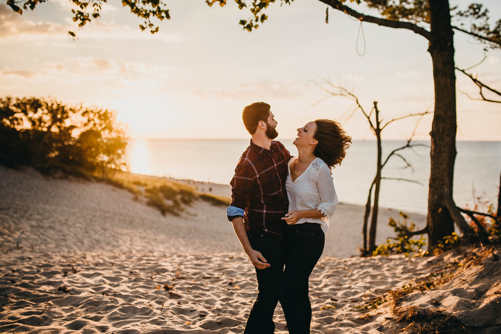 engagement photo of couple on top of sand dune at sunset