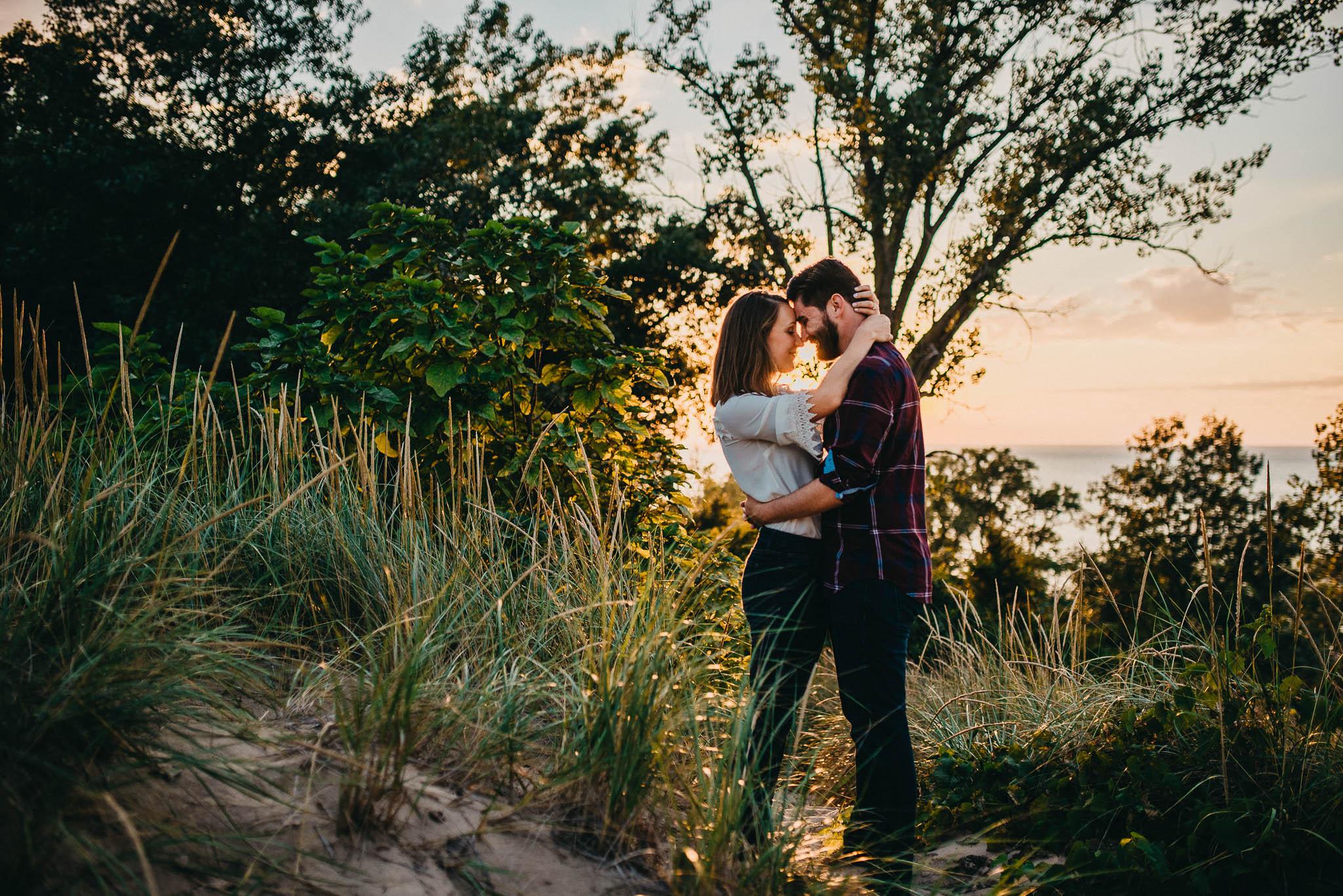 couple standing on sand dune at sunset near Lake Michigan