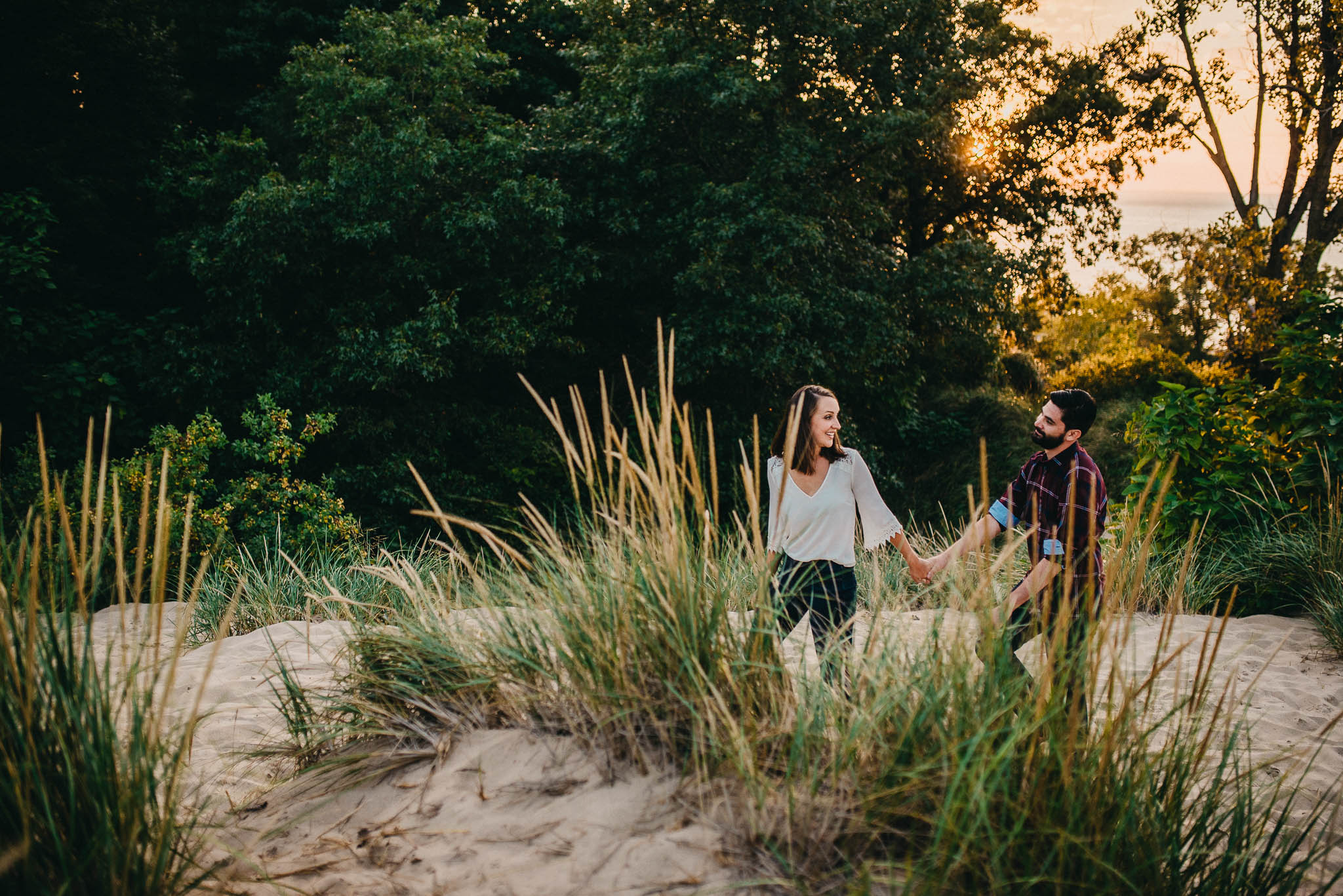 engagement photo of couple walking in sand