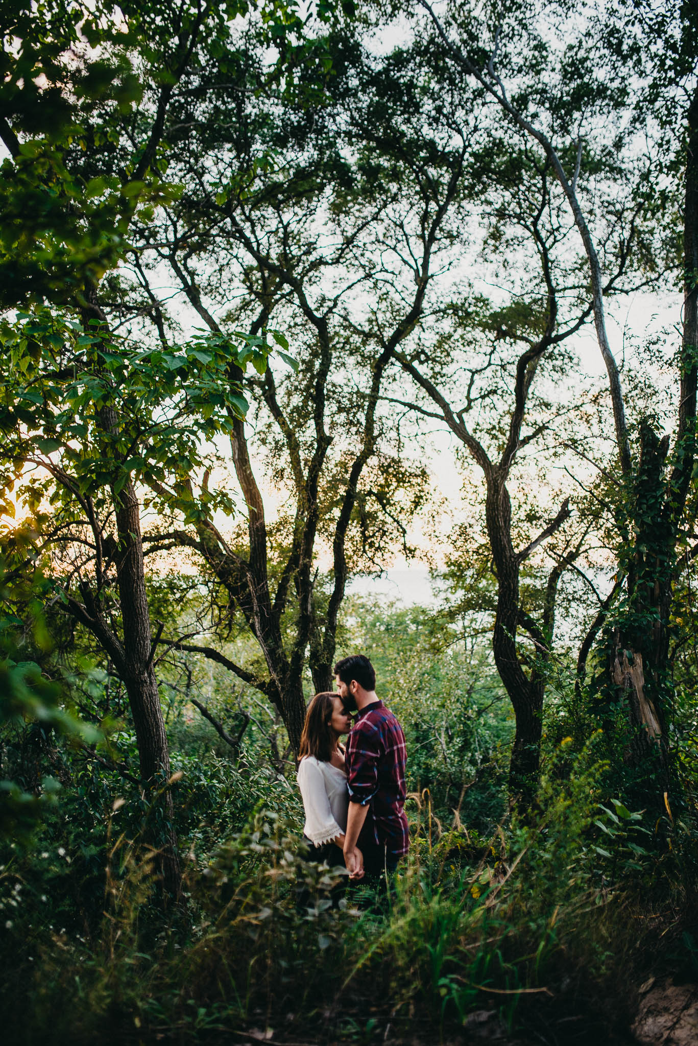 man kissing woman's forehead in the forest during sunset