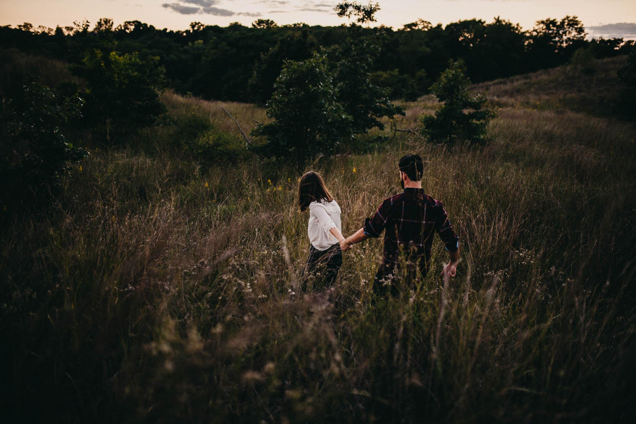 woman leading man through tall grass