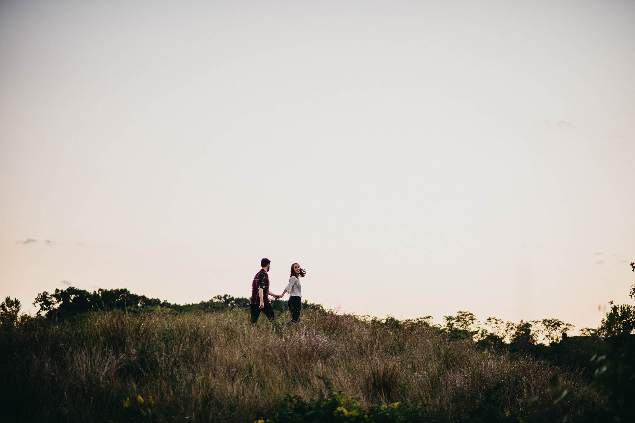 couple walking up a hill in tall grass