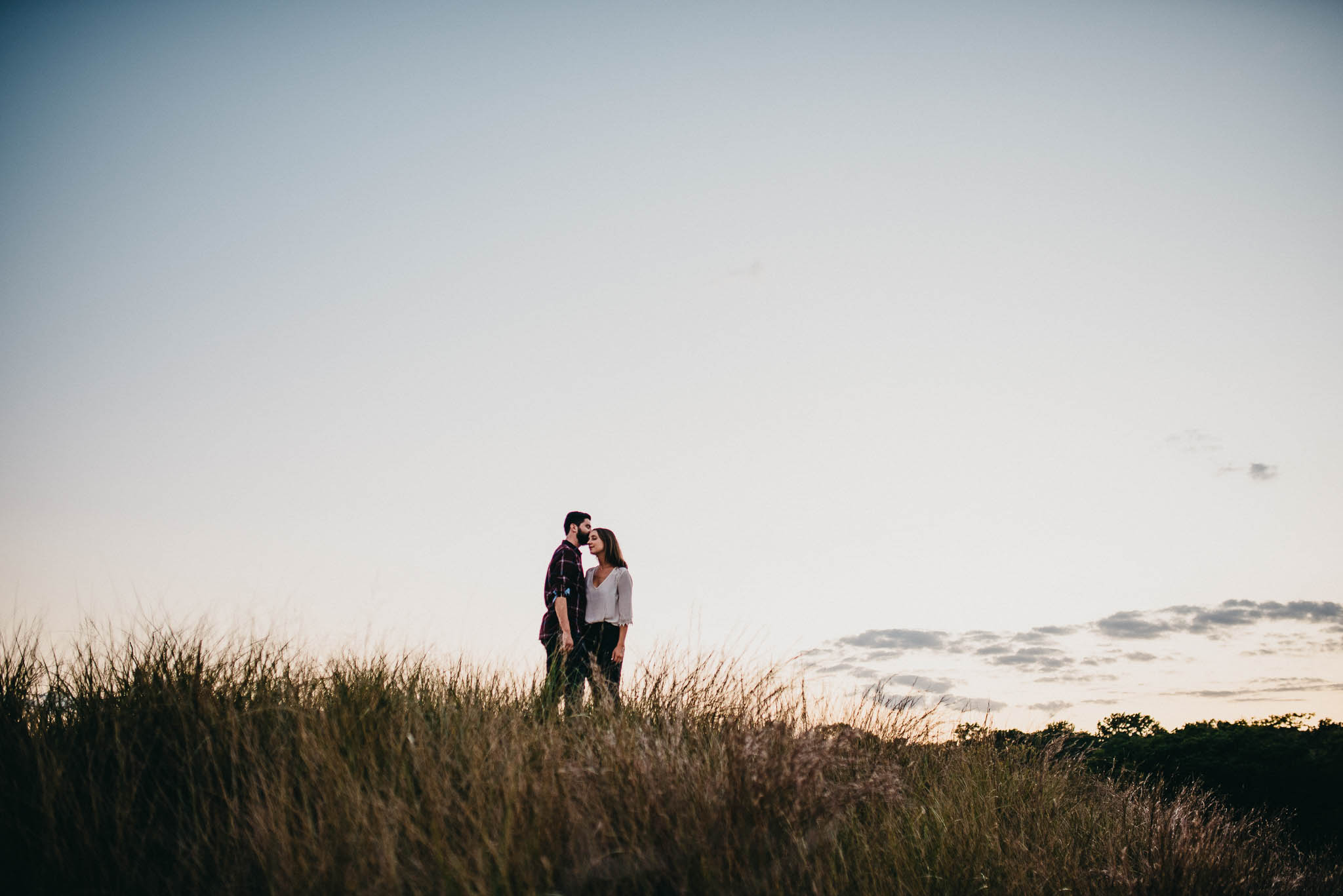 engagement photo of couple embracing on top of hill