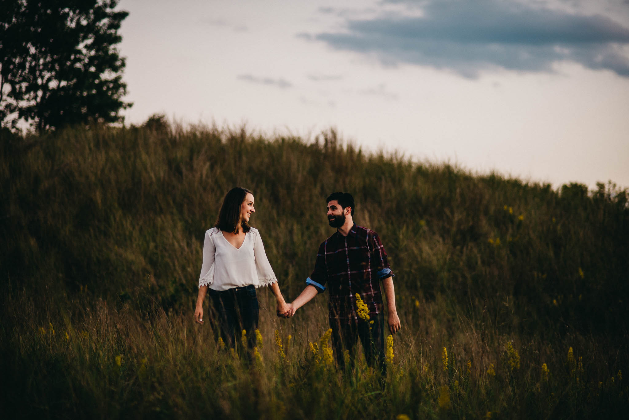 engagement photo of couple walking through field of tall grass