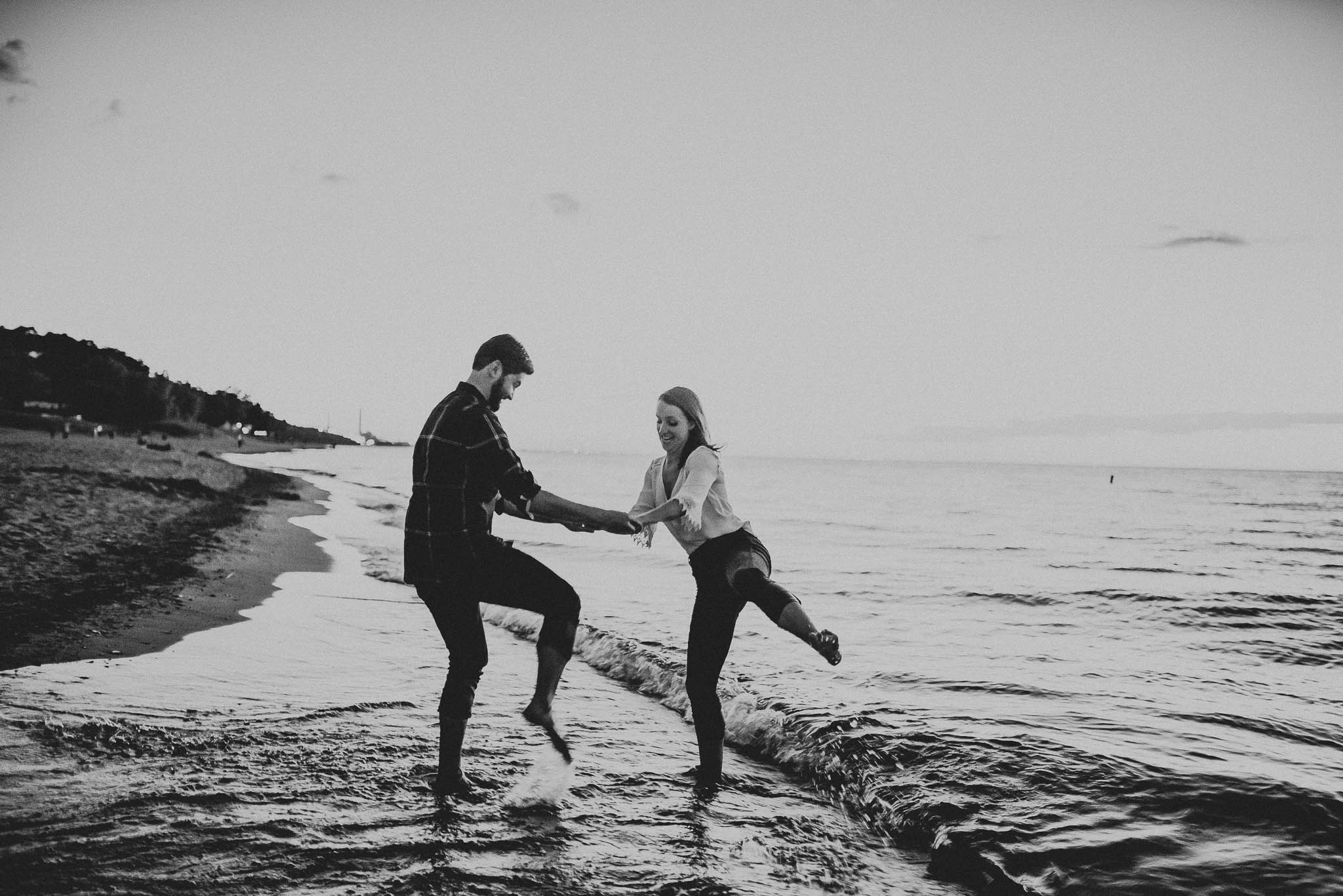 engagement photo of couple trying to splash each other with water