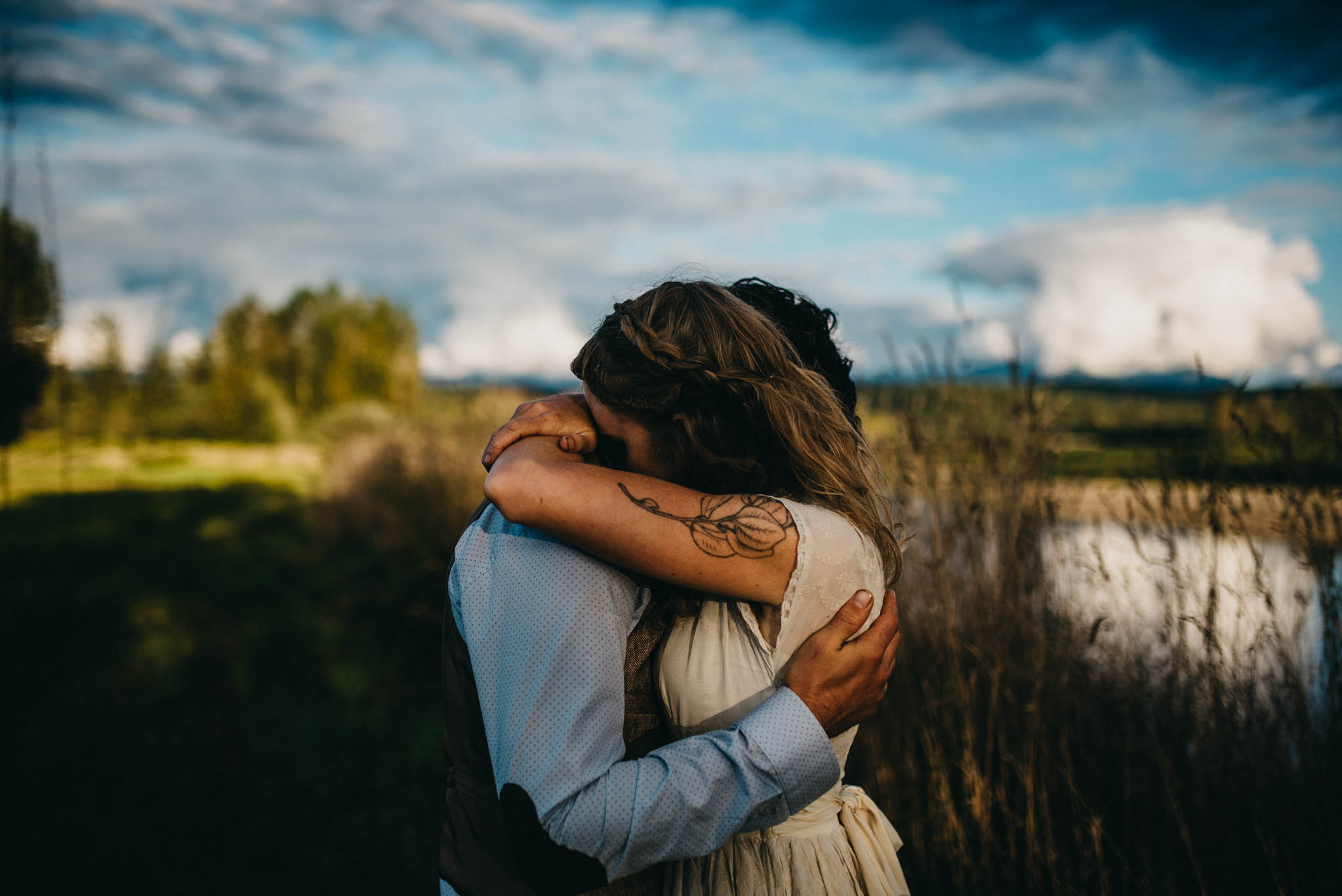 bride and groom embracing during sunset at farm wedding