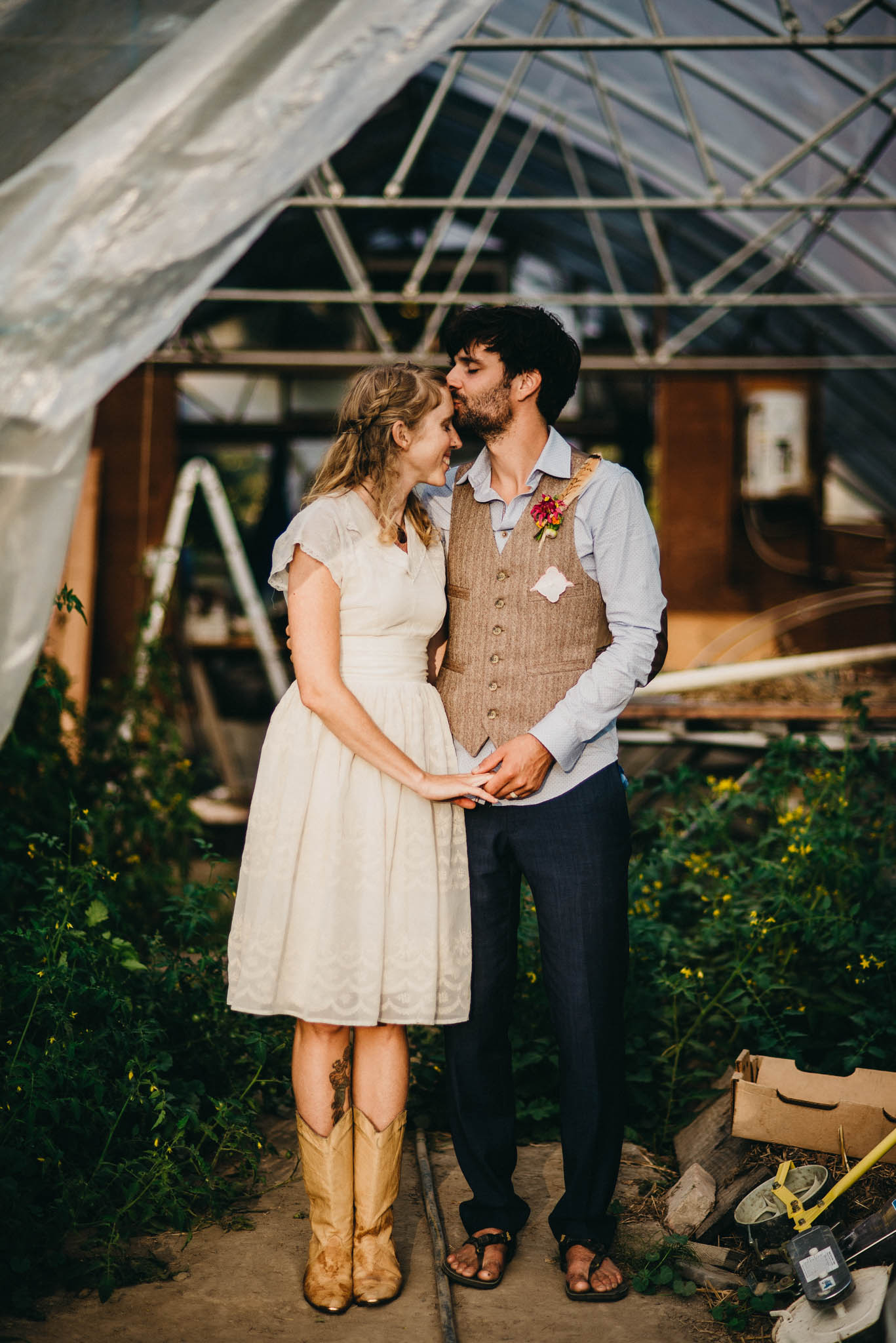 portrait of groom kissing brides forehead in a green house