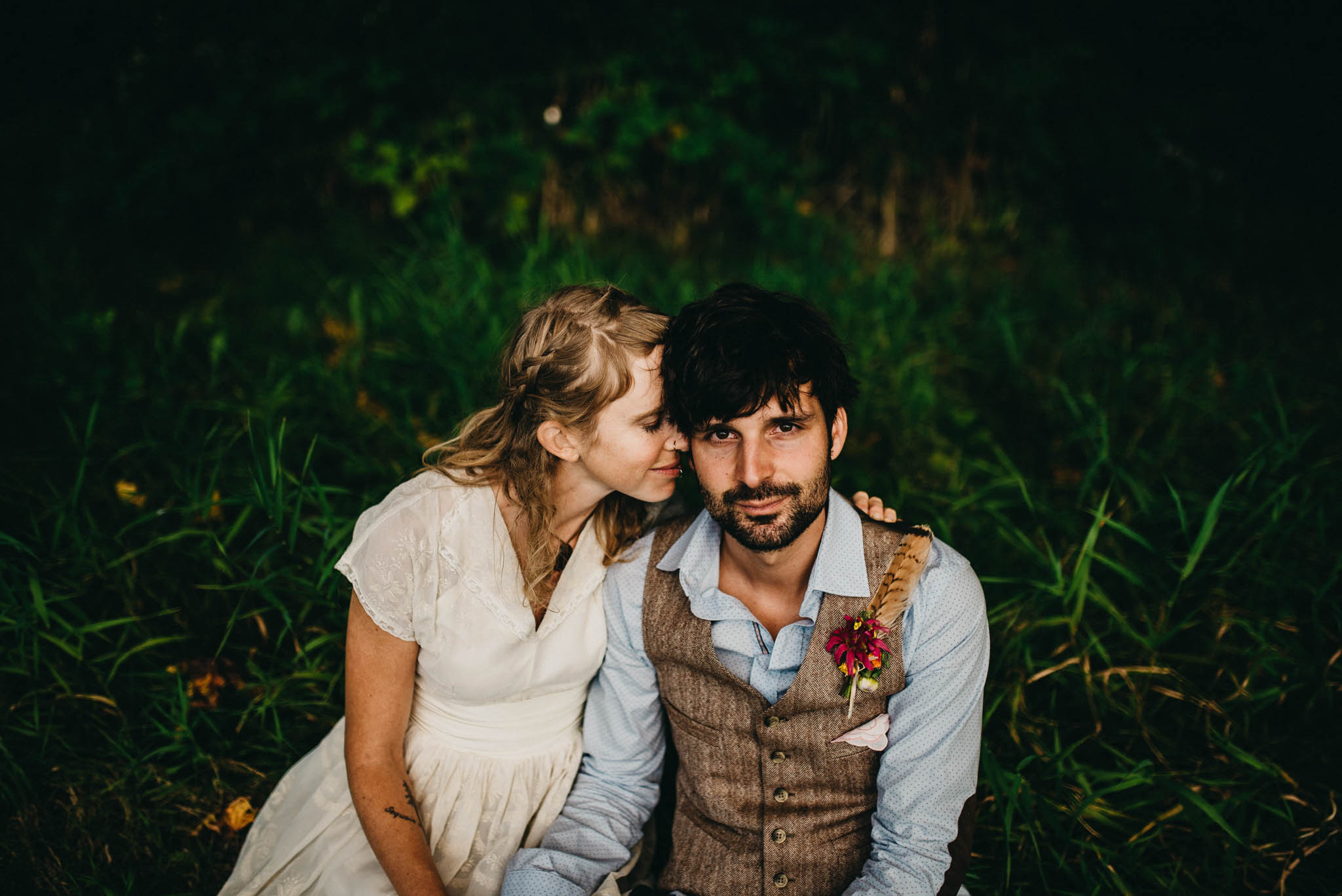 bride and groom sitting in grass